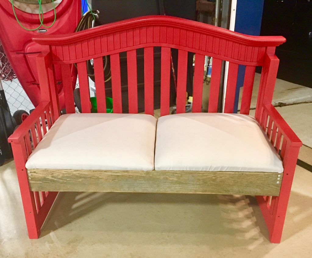 Repurposed headboard and foot board into a couch-like bench. Painted in red chalk paint and upholstered with an up cycled tarp from the roof of a gazebo. Clear coated it can go indoors or outdoors.