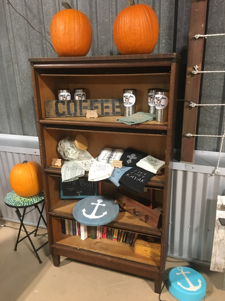 This free bookcase came loaded with books and we used it as a retail display for part of the gift shop. Displaying reclaimed wood wall art and home decor, Embroidered hand towels by TexAna Designs and Captain Jim's travel mugs and UV bracelets.